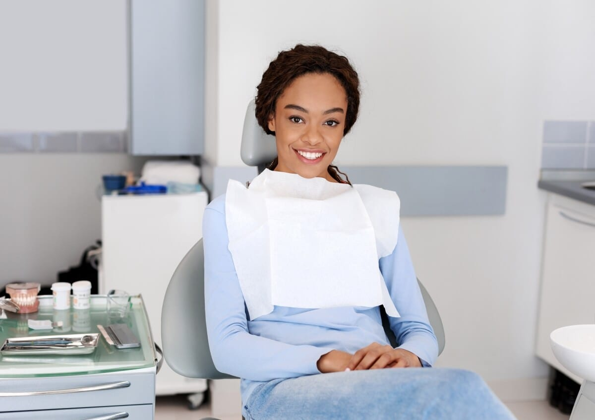 Black Young Famale Pacient Smiling on a Dental Chair AFter Emergency Dental Treatment