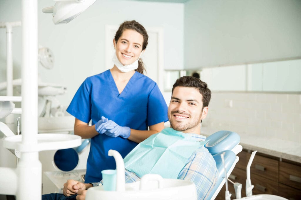 Young Female Dentist offering Support for Dental Emergencies to Her Male Pacient